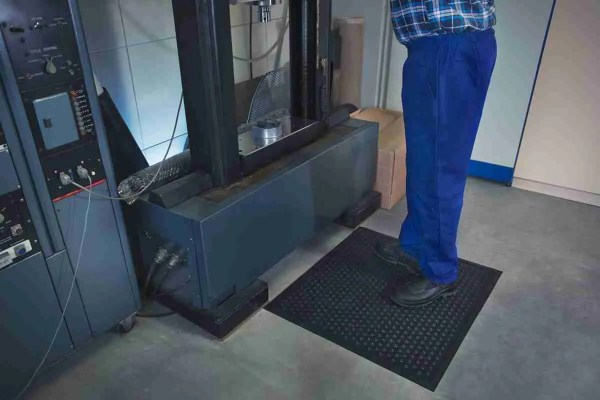 Man at an industrial workstation standing on Morland Comfort Active Industrial Rubber Anti-fatigue mat