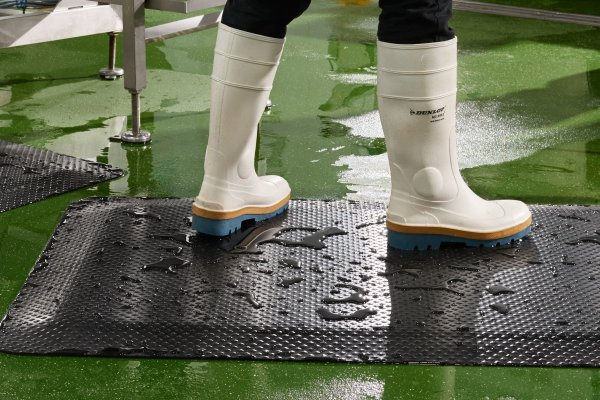 Feet in white rubber boots standing on Morland Comfort Industrial Rubber Anti-fatigue mats