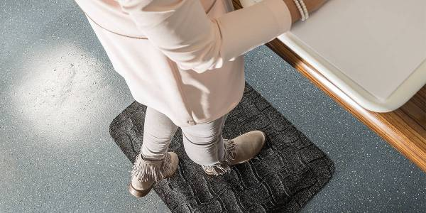 Woman at a standing desk on a Morland Comfort office anti-fatigue mat