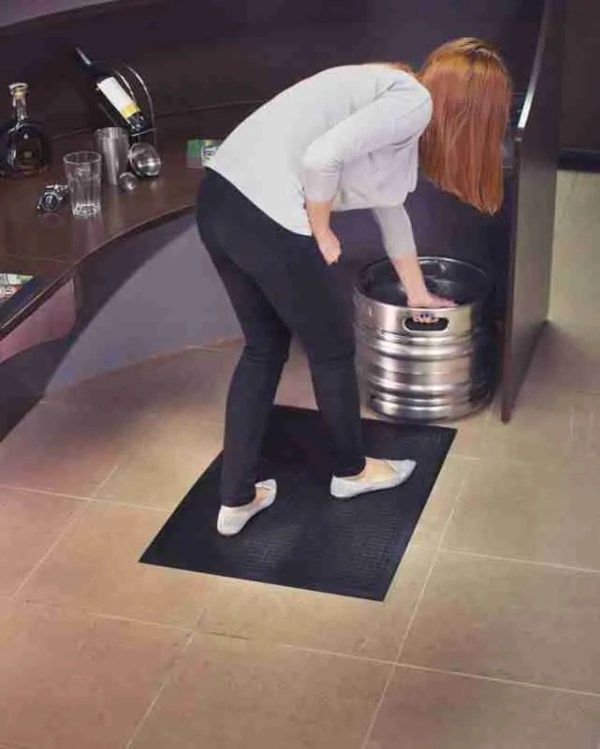 Women standing on a Morland Comfort Structure Anti-fatigue mat bending down and gripping a barrel