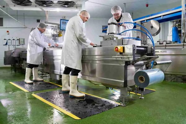 Three workers with white dunlop boots in a food processing area standing on Morland Comfort Safety Anti fatigue mat with water around