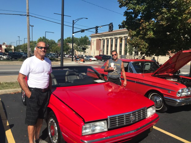 Owners stand by a bright red Cadillac convertible at a car show in Elyria.