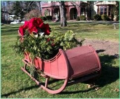 A sleigh full of evergreens and red bows