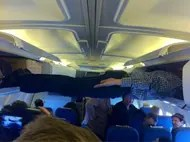 Planking across luggage storage areas of airplane