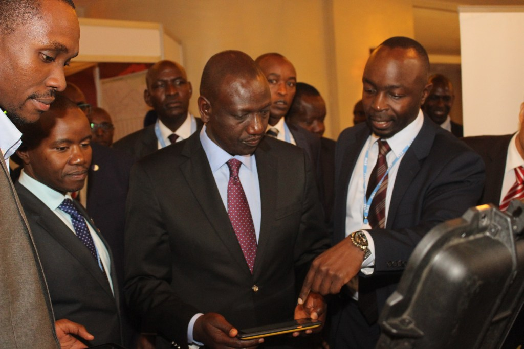 Deputy President, William Ruto and CS of Information, Communications and Technology, Mr. Joseph Mucheru at an exhibition stand with Alex Masika, Head of business development, BRCK Limited
