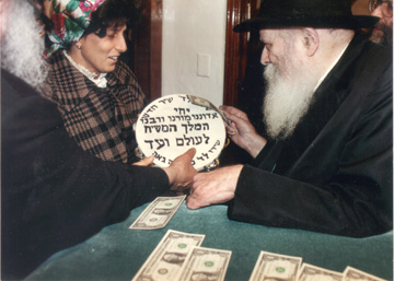 Mrs. Chava Cohen gives Yechi tambourine to the Rebbe