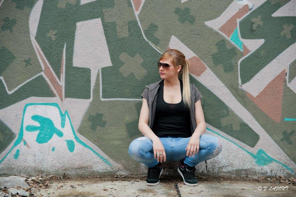 Rose pose devant un mur de tag