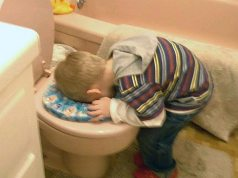 Boy sticking head in toilet