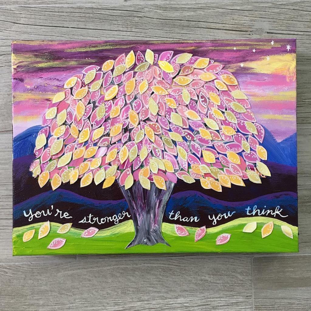 """Painting with a 2-D cut paper tree with pink, yellow and purple leaves with the words """"You're Stronger Than You Think"""" over a deep blue background."""