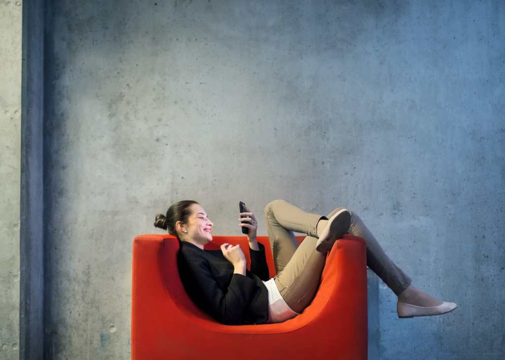 A young businesswoman with smartphone sitting on red armchair in office.