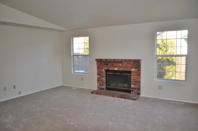 before house tour  empty living room with brick fireplace and two windows