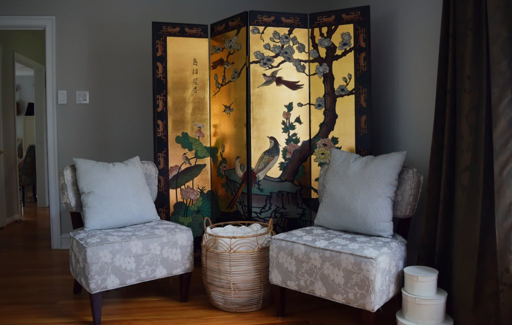 floral chairs and basket in front of gold chinoiserie coromandel floor screen