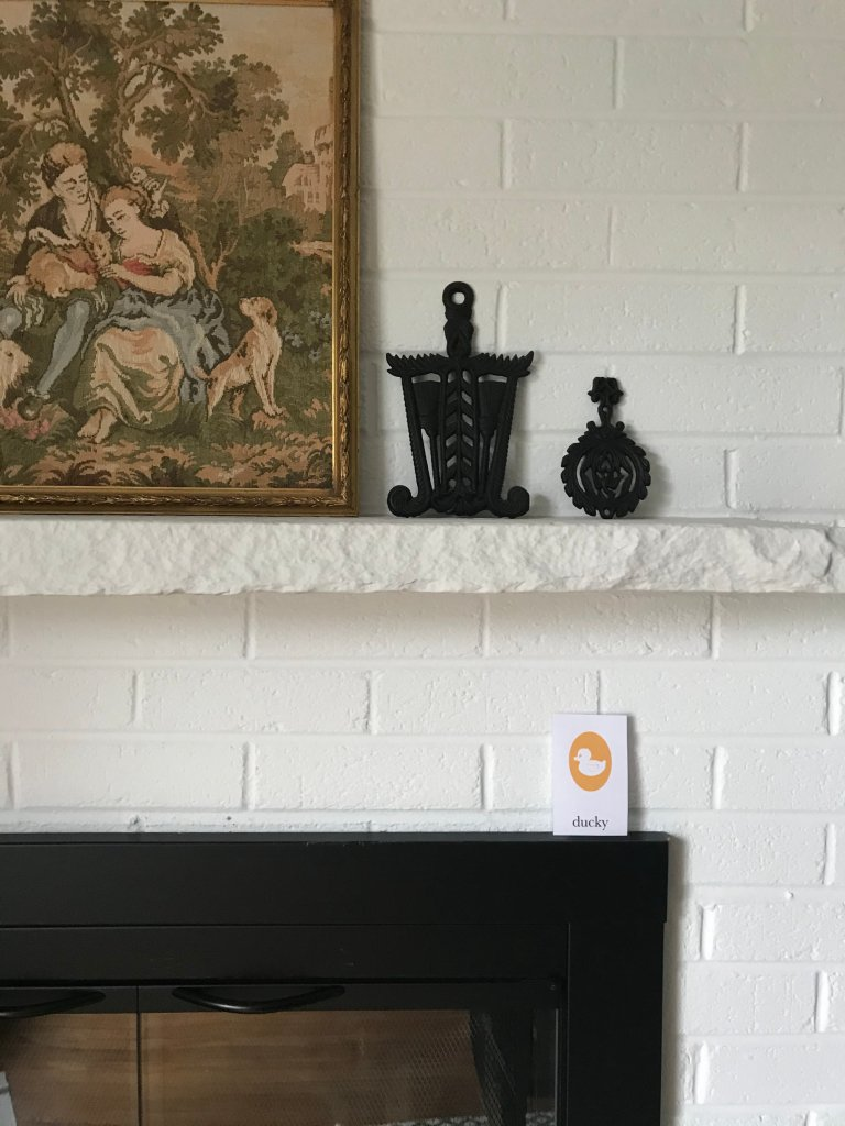 rubber ducky flashcard on white brick fireplace