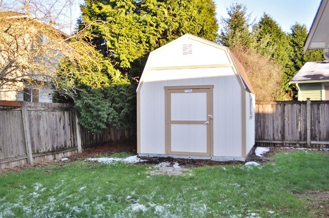 cream shed with tan trim in yard