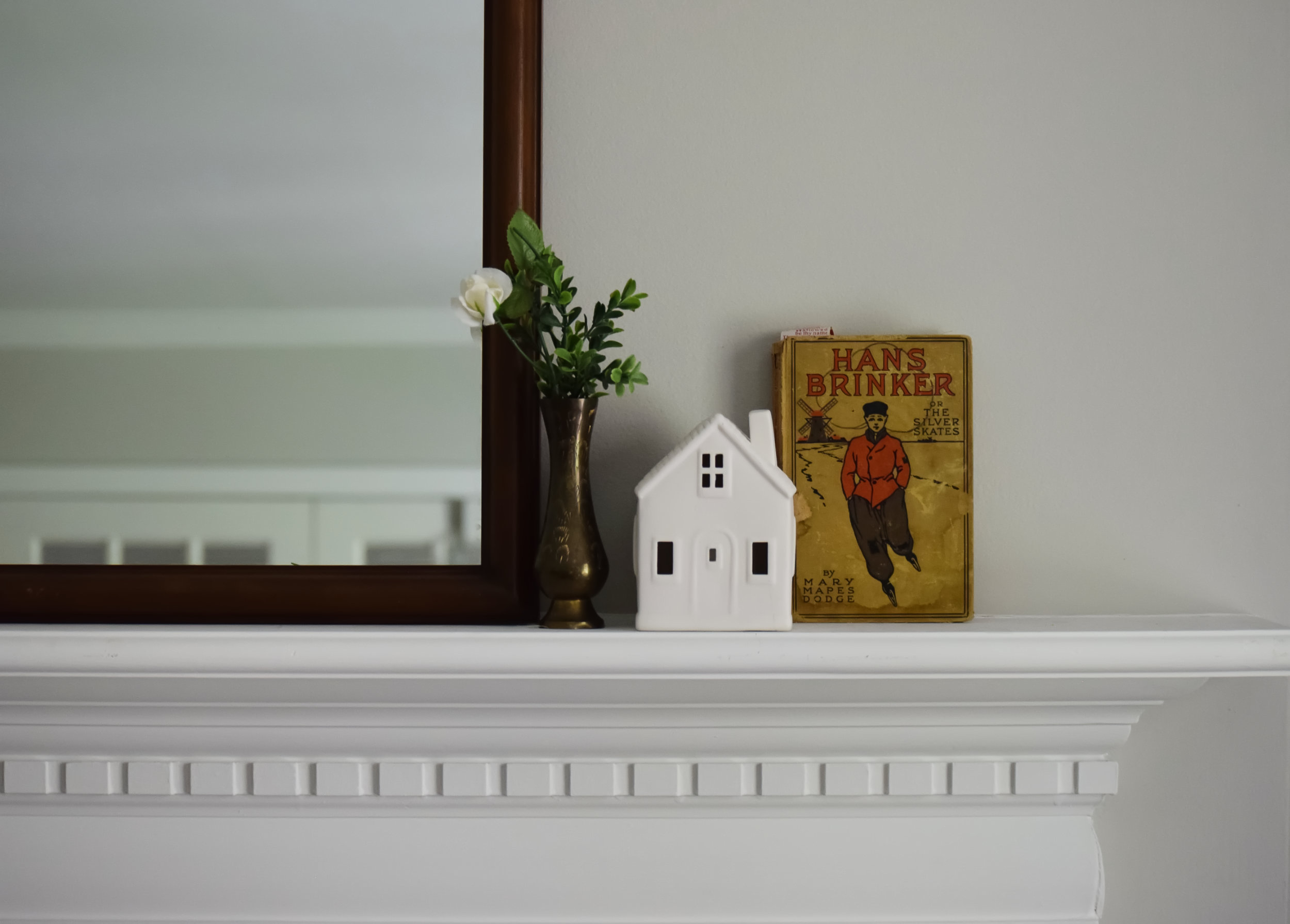hans brinker book ceramic house and flowers in vase next to mirror on white fireplace mantel