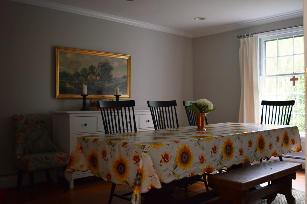 sunflower tablecloth in gray dining room cross in window with grids