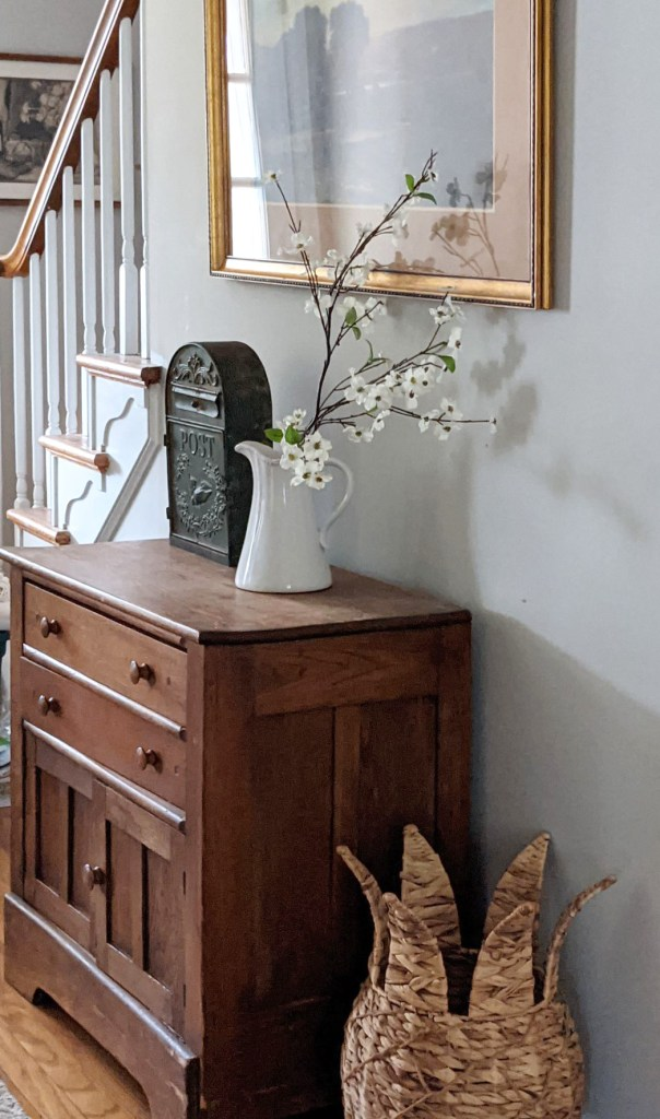 white branch in vase on entryway antique cabinet