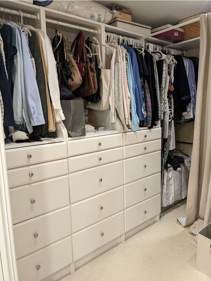 hanging clothes and drawers in walk in closet in progress