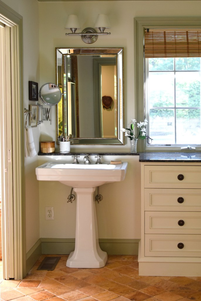 accordion mirror by pedestal sink in master bathroom 1