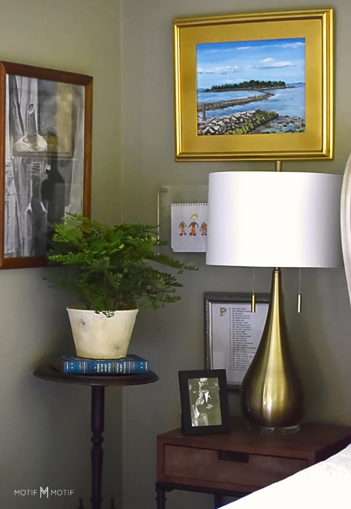 gallery wall around bedside table with potted plant on stand and books