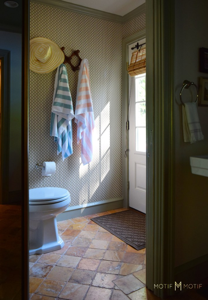 water closet with geometric wallpaper and accordion towel rack