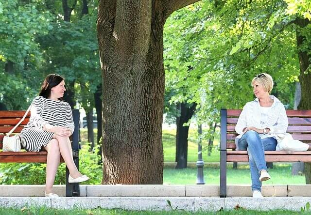 Two ladies are talking to each other while sitting on a bench in a park - How to Live a Happy Life Along with Motivation - Outstanding Way - Motivational Blogs - Motivation N You