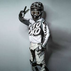 Front view of model wearing grey and white camo motocross jersey with peace sign