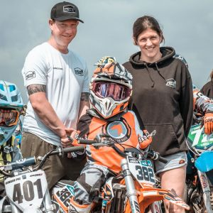 photograph of mum and dad with son sitting on motocross bike wearing orange fresh motorsport kit