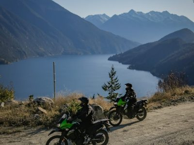 Motorcycle riding dusty switchbacks between Shalath and Seton Portage with Seton Lake in the background