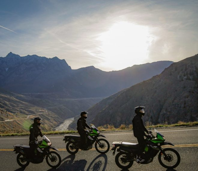 3 Kawasaki Motorcycles cruising on a paved road in Lillooet during a motorcycle tour