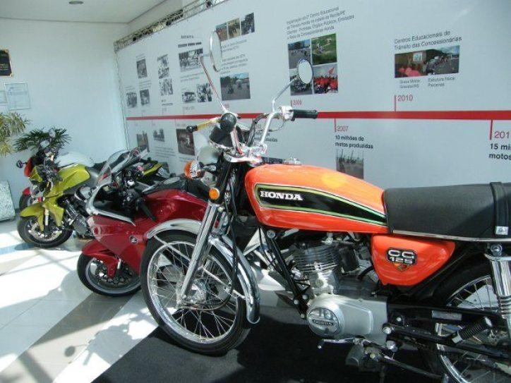 """Na recepção do CETH (Centro de Educação de Trânsito Honda) em Indaiatuba, 36 anos de história estão expostos..... na parede. De moto """"antiga"""" mesmo, só a primeira CG 125 fabricada no Brasil, em 1976 - esta laranjinha no primeiro plano."""
