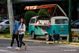 Two mexican pedestrians, a man and a smiling girl, crossing the street in front of a VW van that has been converted to a food stall