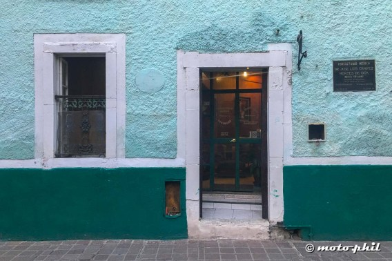 Door and window in a green and turquoise wall with white accents