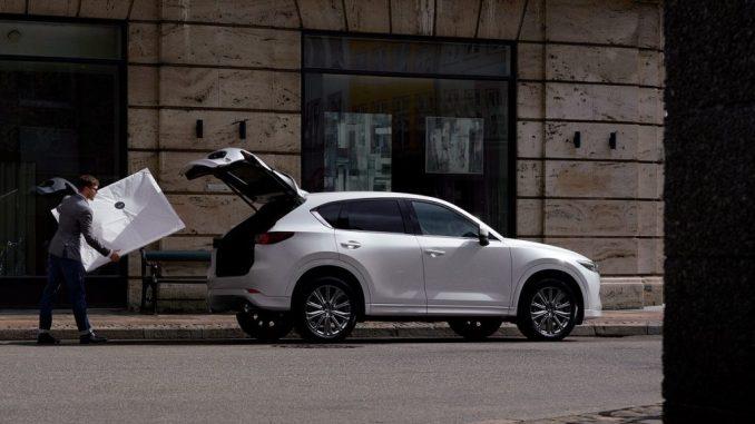 رجل يحمل طردًا كبيرًا في صندوق سيارة مازدا CX-5 بيضاء 2022.