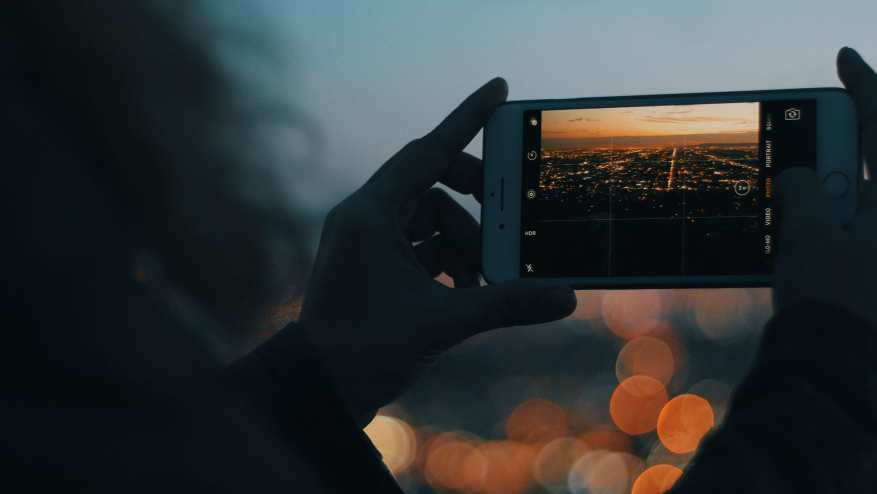 Woman taking a sunset image of the Los Angeles skyline. Smartphones are a big part of our photograpy for motorcycling kit list.