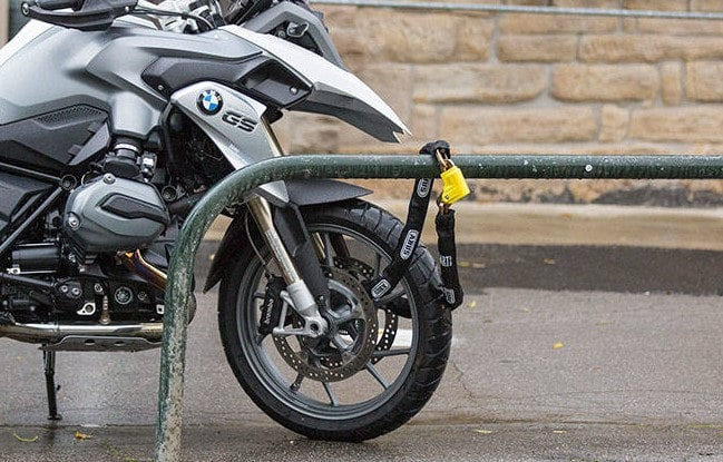 bmw motorcycle secured to fence with lock and chain - motorcycle security