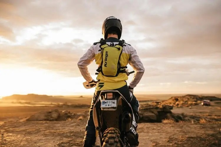 off-road biker in desert with hydration pack