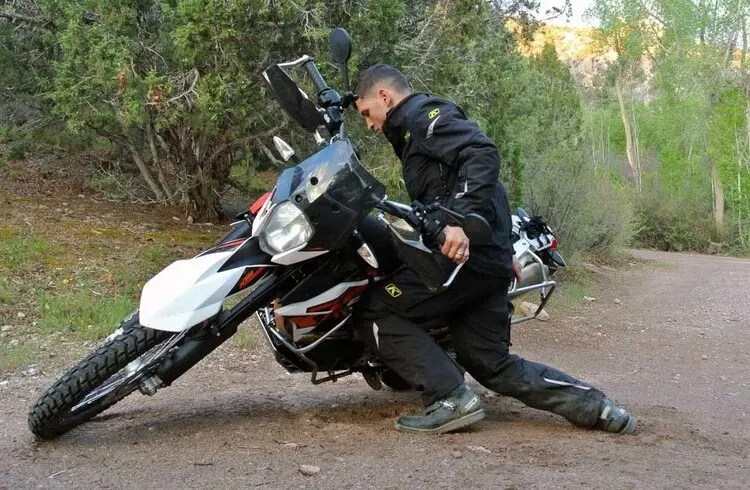 biker picking up bike after fall