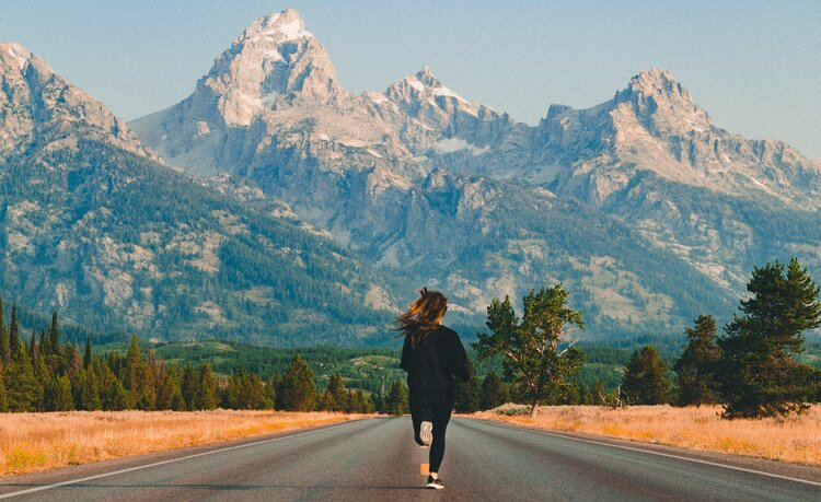woman running for fitness on road with mountains