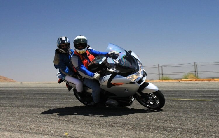 bmw rider with pillion - cornering a motorcycle