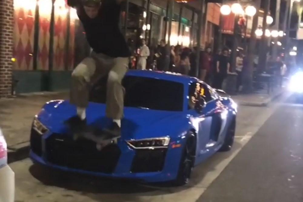 Skateboarder jumps on Audi R8