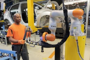 Car Workers and Mini Robots Work Hand in Hand