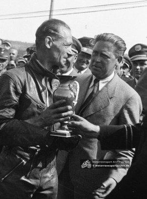 James Guthrie after winning the Grand Prix of Europe at the Sachsenring in 1936. Next to him is the mysterious figure of J.A. Woodhouse, an Englishman who lived in Germany and worked for the Nazis. He was later wanted by them during WWII and appeared in The Black Book, a secret list of prominent British residents to be arrested.