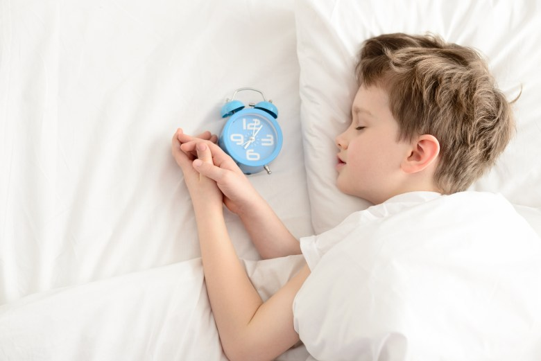 Top view of little boy sleeping in white bed with alarm clock near his head. Sleeping boy. Sleeping child