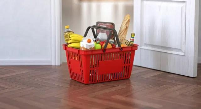 Shopping basket sitting on wood floor full of groceries