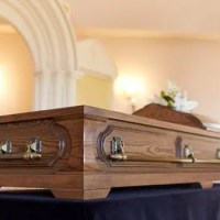 Wood casket sitting on table in funeral home