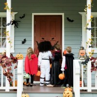 Kids standing at front door trick-or-treating