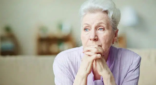 Elderly woman with hands folded staring off into the distance.