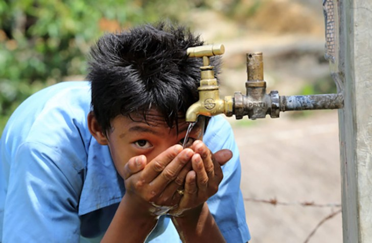 Mitra Rana Magar drinks from a tapprovided by theNEWAH WASH water project in Puware Shikhar, Nepal.