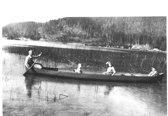 Alfred Barnfield on Alta Lake with daughter Vera and two sons (either Fred, Bill, or Charlie). Homemade canoe used to deliver dairy products to Rainbow Lodge and local families. Circa 1920.